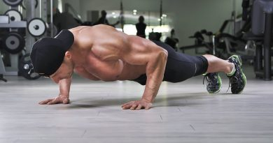 Handsome powerful athletic man performing push ups at the gym. Strong bodybuilder with perfect back, shoulders, biceps, triceps and chest.